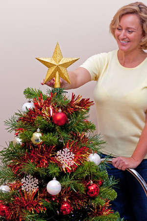 placing:  woman standing on a ladder placing the star on top of her Christmas tree