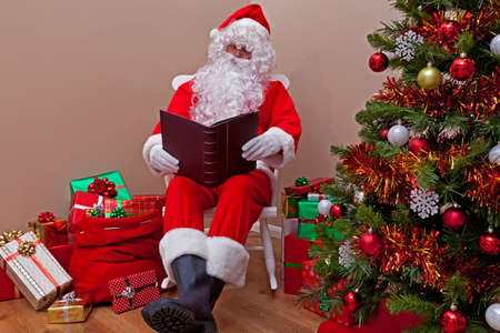 Santa Claus sat in a rocking chair reading the 'naughty or nice' list surrounded by gift wrapped presents. photo