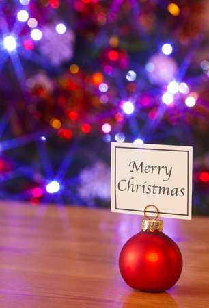 A red bauble placeholder with a card saying Merry Christmas, fairy lights blurred on the Christmas tree behind. Stock Photo - 16379866