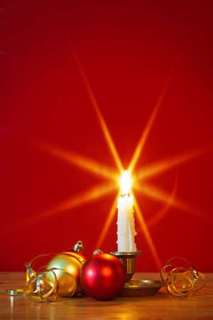 A lit candle in brass holder with Christmas decorations and red background, star filter used during capture for the flame. Copy space to add your own text. Stock Photo - 16379865