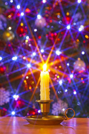 lit candle: A dripping wax candle in brass holder against a Christmas tree with decorations and fairy lights, star filter used during capture to create a starburst on the lights.
