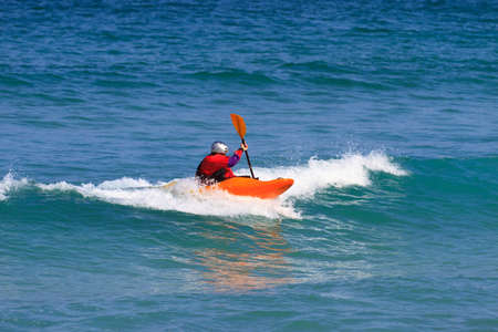 Man in a white water single kayak wearing a dry top and helmet as he rides the wave in open sea using his paddle to control his direction. Stock Photo - 16301989