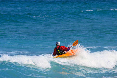 watersports: Man in a white water single kayak wearing a dry top and helmet as he rides the wave in open sea using his paddle to control his direction.