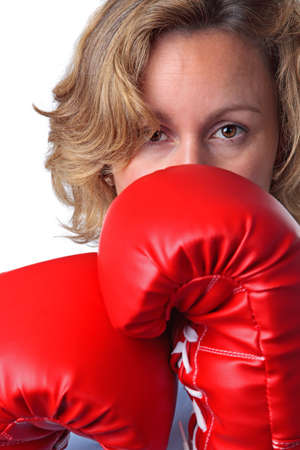 retaliation: Close up of a woman who is weaing boxing gloves, white background.