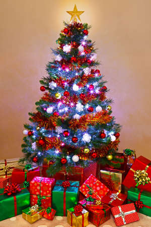 photo of a decorated christmas tree lit up with fairy lights and surrounded by gift wrapped