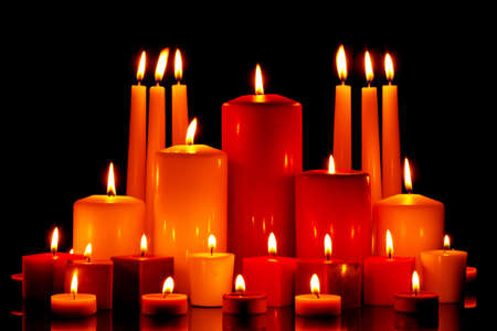 A large group of mixed size and shape candles burning with bright flames on a black background. Stock Photo - 16379873