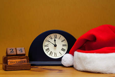 A hall table clock shows it's close to midnight on Christmas Eve, with desk calendar and Santa Claus hat. photo