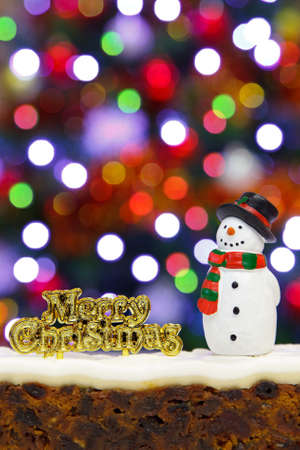 A Christmas cake with a Snowman and a Merry Christmas message, with blurred fairy lights in the background from a Christmas tree. Stock Photo - 16541225
