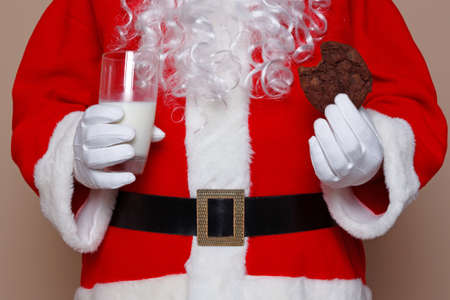 Santa Claus holding a glass of milk and a chocolate cookie.