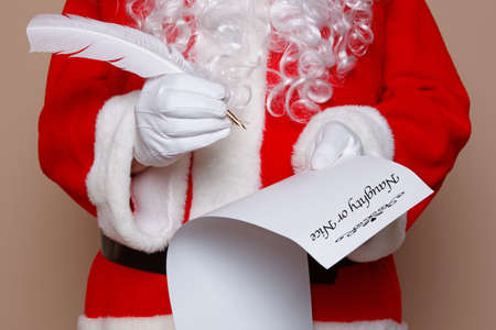 in nice: Santa Claus holding a quill pen whilst checking the naughty or nice list. Stock Photo
