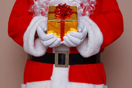 Santa Claus holding a gift wrapped present with gold wrapping paper and a reb bow and ribbon. Stock Photo - 16522717