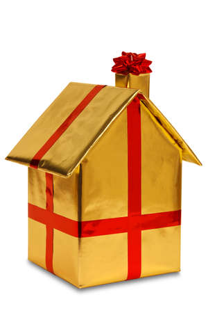 A new home wrapped in gold paper with red ribbon and bow, isolated on a white background. Good image for house buying or other property related themes.