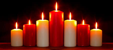 christmas illuminations: Still life photo of red and white church candles arranged in an arch burning with bright flames against a black background.