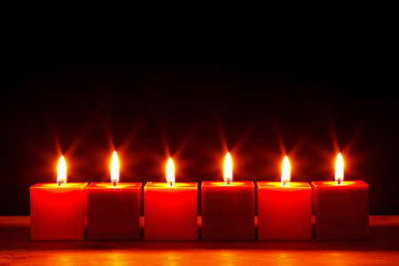 Still life photo of six square red candles burning bright against a black background.