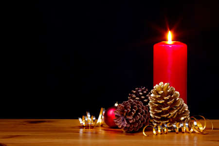 lit collection: Still life photo of a Christmas candle burning bright with gold pine cones and ribbon plus a red bauble, copy space on the black background to add your own text. Stock Photo