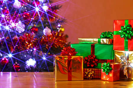 Gift wrapped Christmas presents on a table and a decorated tree behind with fairy lights illuminated, Stock Photo - 16663274