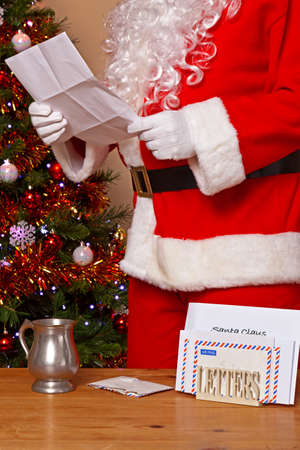 Santa Claus reading a letter at his home in the North Pole, a decorated tree in the background and a mug of hot chocolate on the table. Stock Photo - 16640825