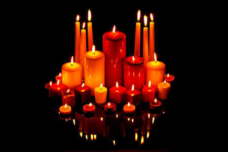 A group of red and white Christmas candles on a black reflective surface Stock Photo - 16663272