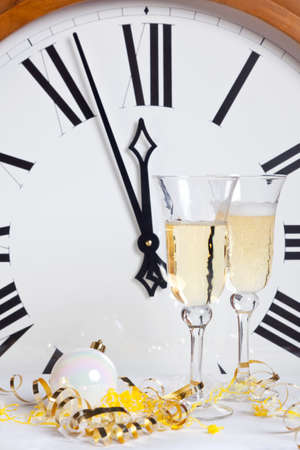About to strike midnight on New Year Eve with champagne glasses and streamers in front of a large clock face. photo