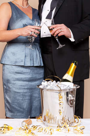 A couple in evening wear touching glasses for a Champagne toast, good image for New Years Eve, Wedding or Celebration themes. photo