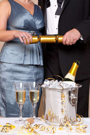 christmas cracker: A couple in evening dress pulling a gold Christmas cracker at a Champagne party.