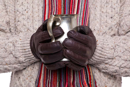 pewter mug: Close up of a man in woolen jumper, scarf and gloves holding a pewter mug of hot mulled wine. Focus is on the hands and tankard.