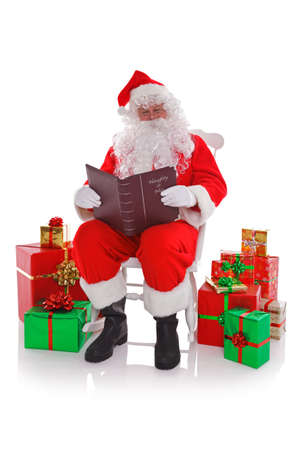 santa outfit: Santa Claus sat in a rocking chair surrounded by gift wrapped presents as he reads the Naught or Nice list, isolated on a white background.