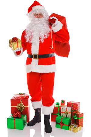 Santa Claus holding a sack full of gift wrapped presents ready to deliver, isolated on a white background. photo