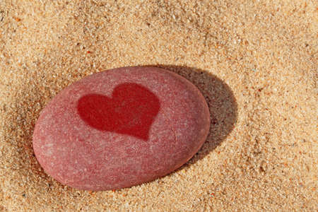 heart in sand: A red pebble on a beach with a wet heart shape upon it.