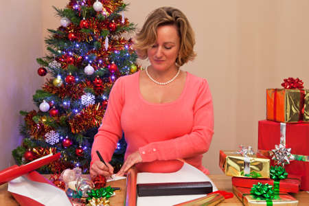A woman at home wrapping her Christmas presents and writing a gift tag. Stock Photo - 16970722