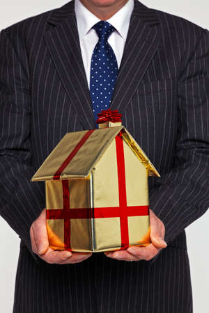 A businessman presenting a new home gift wrapped in gold paper with ribbon and bow. Good image for house buying related themes. Stock Photo - 16970727