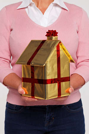 New home concept image of a woman in casual clothing holding a house gift wrapped in gold paper with red ribbon and bow. photo