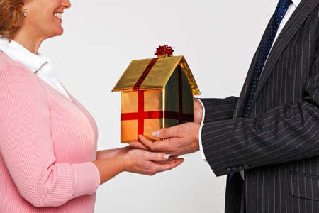 A businessman giving a woman a new home wrapped in gold paper with red ribbon and bow. Good image for house buying themes. photo