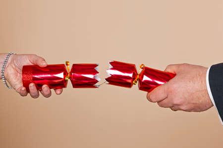 crackers: A las manos del hombre y de los womans que tiran de una galleta de Navidad rojo. Foto de archivo