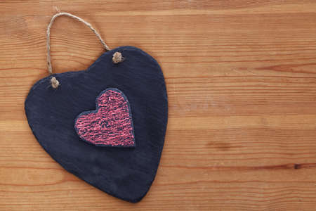 Two heart shaped slates one with red chalk on an old wooden background. photo