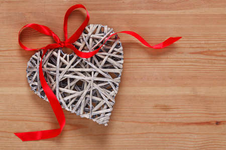 A heart shaped wicker decoration with red ribbon on a rustic wooden background. photo