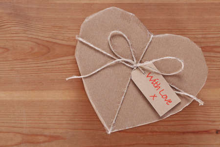 A heart shaped brown paper parcel with a label saying With Love. photo