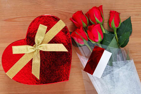 Chocolates in a heart shaped box and a bunch of red roses with card on an old wooden table. Stock Photo - 16957144