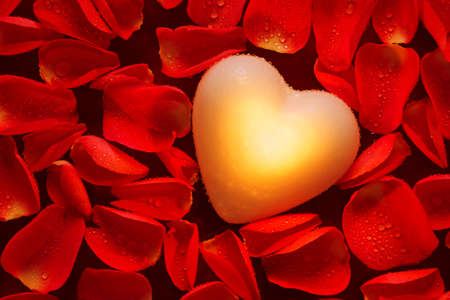 A glowing heart in amongst wet red rose petals floating on water. Stock Photo - 16957126