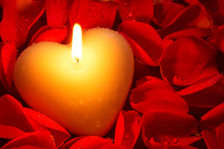 A heart shape candle surrounded by red rose petals covered in water droplets, a good image for a Valentines day or other romance related theme. Stock Photo - 16957119
