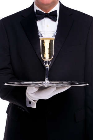 champagne flutes: A butler serving a glass of champagne on a silver tray, on a white background. Stock Photo