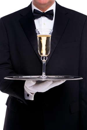bandejas: Un mayordomo que sirve una copa de champ�n en una bandeja de plata, sobre un fondo blanco.