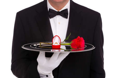 serving tray: A butler holding a silver tray upon which is a diamond engagement ring in a heart shaped jewelry box and a single red rose, on a white background.
