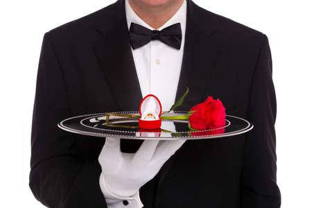 trays: Un mayordomo que sostiene una bandeja de plata sobre la que es un anillo de compromiso de diamantes en una caja en forma de coraz�n joyas y una sola rosa roja, sobre un fondo blanco.