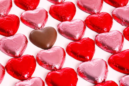 Chocolate hearts in red and pick foil wrappers on a white background, with one unwrapped heart in amongst the group.
