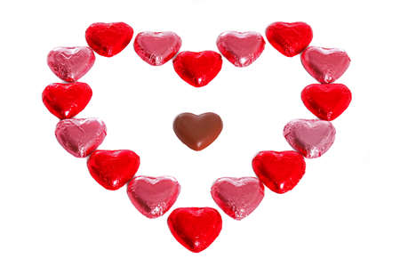 A heart made out of foil wrapped chocolates with an unwrapped one in the middle, white background. Stock Photo - 17226325