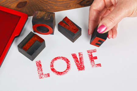 inkpad: A woman using wooden letterpress blocks to print the word LOVE in red ink on white paper.