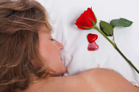 A woman is sleeping whilst a single red rose and heart shaped chocolates have been left on her pillow for Valentines day.  Stock Photo - 17221321