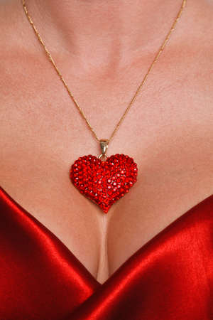Close up of a woman wearing a red crystal heart shaped necklace and red satin dress. Stock Photo - 17221323