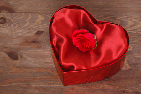 A single red rose in a heart shaped box with red satin lining against a rustic wooden background. Stock Photo - 17372624